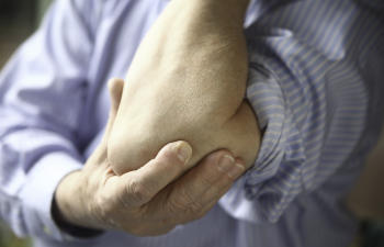 man suffering from tennis elbow pain