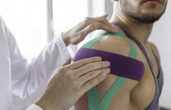 Rehab Specialist Applying Kinesiology Tape Over a Sportsman Shoulder